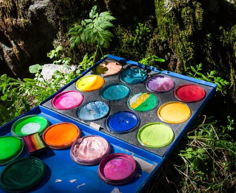 Caso compacto del ` s del pintor del vintage en hierba con la paleta, las herramientas artísticas y la pintura abstracta foto de archivo libre de regalías