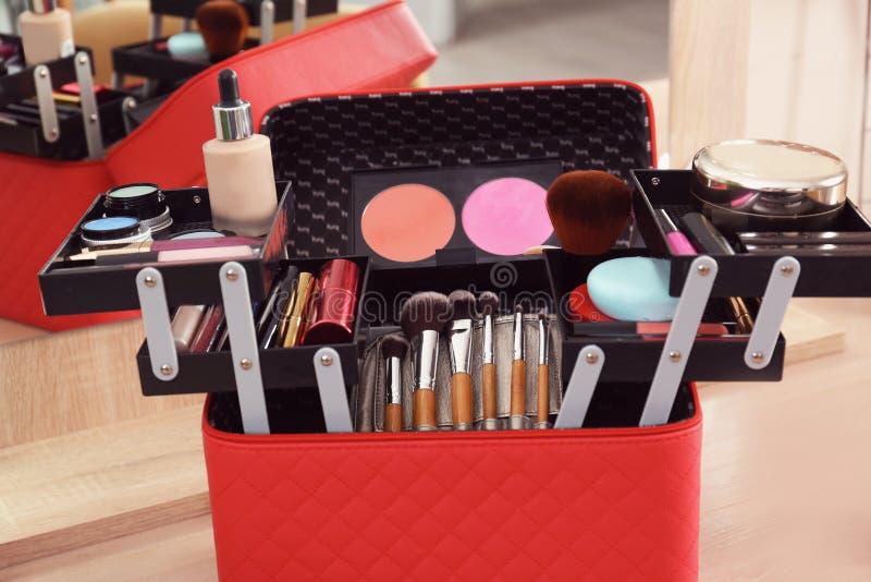 Caso del cosmetólogo con los productos y las herramientas profesionales de maquillaje en la tabla de madera imagen de archivo