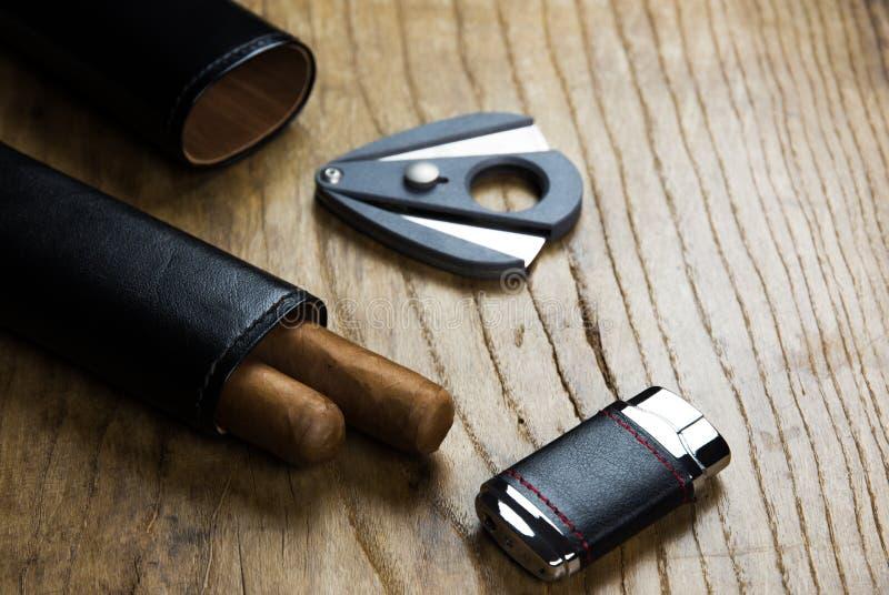 Caso di cuoio con i sigari e la taglierina di sigaro e dell'accendino fotografia stock