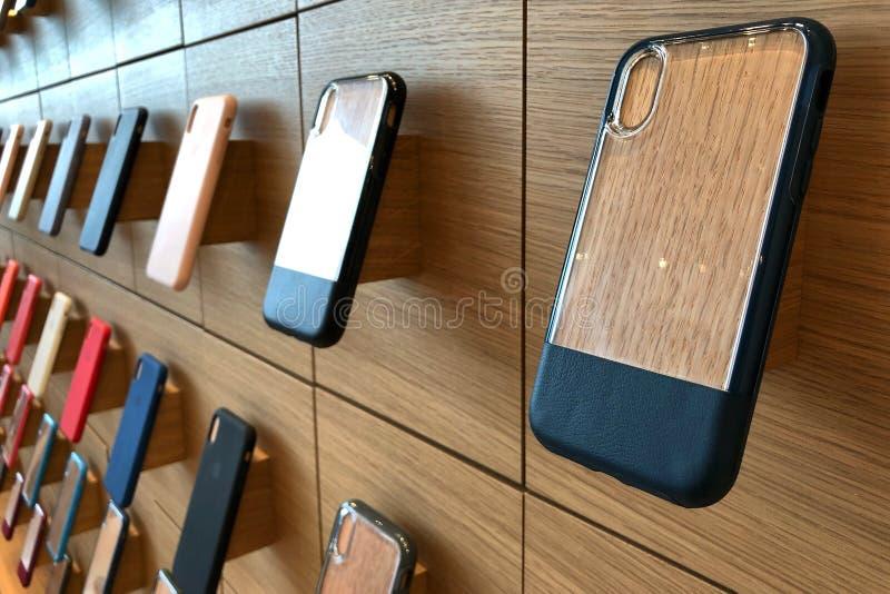 Casos da série do iphone X de Apple que penduram na parede na loja de Apple fotos de stock