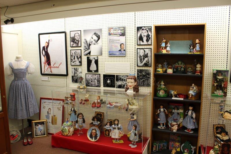 Casos de vidro e diversas prateleiras que levam a coberta histórica mágico de Oz amado da recordação, todo o museu da onça das co fotografia de stock