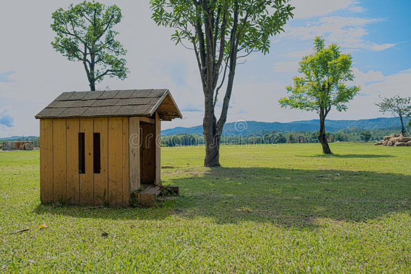 A casota de madeira está em um prado com grandes árvores fotografia de stock