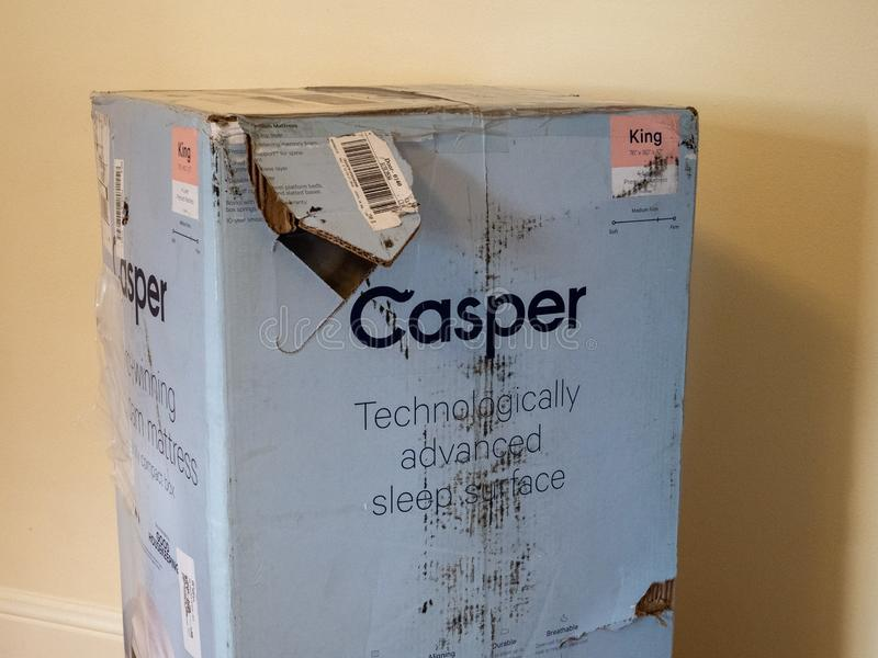 Casper home mattress delivery box inside home. Weathered and damaged from shipping and freight stock image