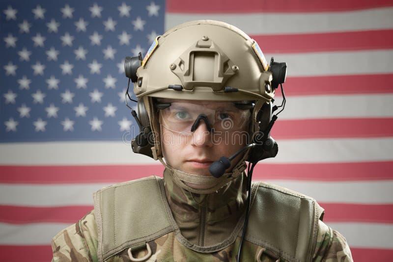 Casque de port de jeune militaire avec le drapeau des Etats-Unis sur le fond photos stock
