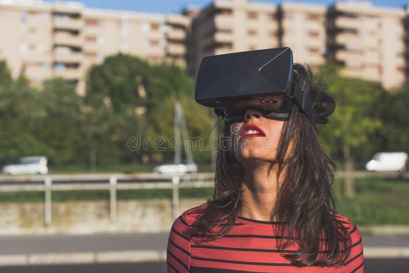 Casque de port de réalité virtuelle de belle jeune femme photos stock