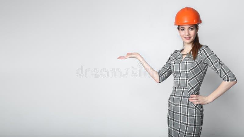 Casque de port de sourire de constructeur de femme d'affaires dirigeant le doigt sur l'espace de copie photo stock