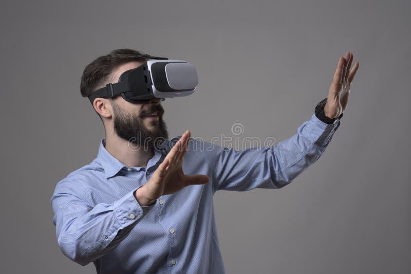 Casque de port stupéfait de vr de réalité virtuelle de jeune homme occasionnel futé barbu adulte faisant des gestes des mains et  images stock