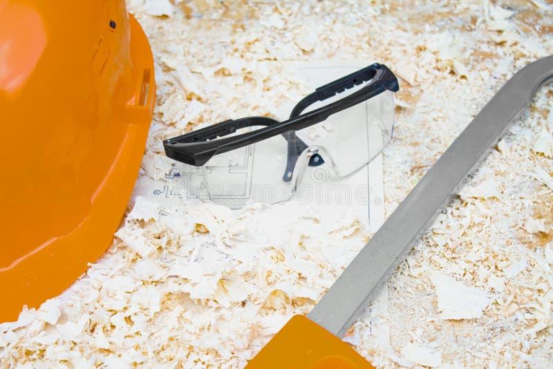 Casque de sécurité avec des verres et une scie sur le fond du concept de sciure sur le sujet de la construction et de la réparati photo libre de droits