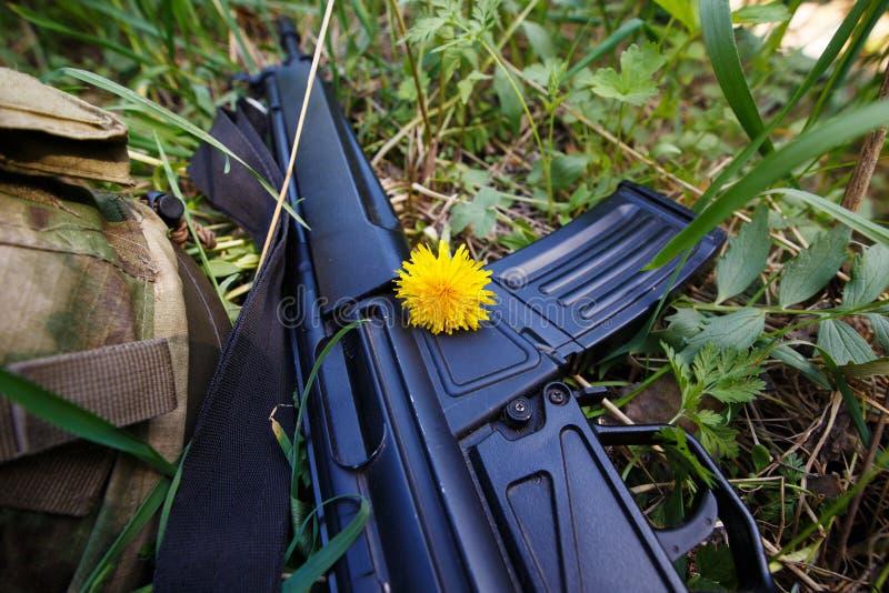 Casque militaire, fusil et une fleur dans l'herbe photo stock