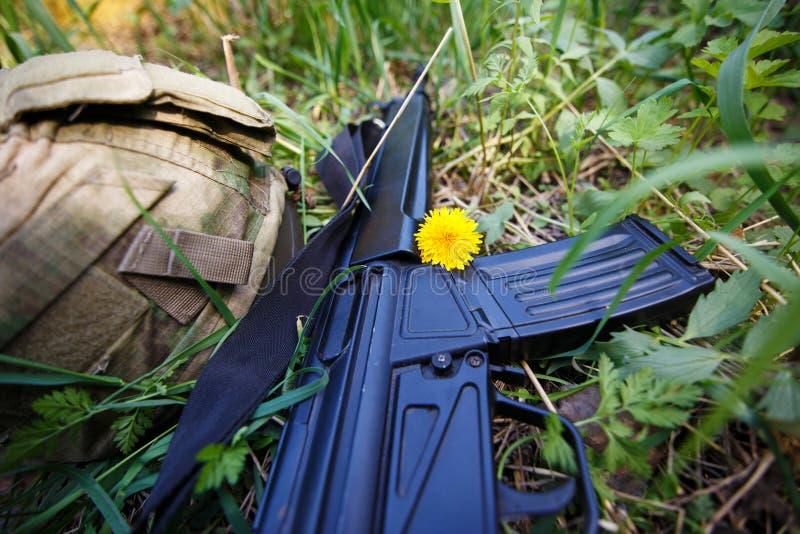 Casque militaire, fusil et une fleur dans la fin d'herbe  photos libres de droits