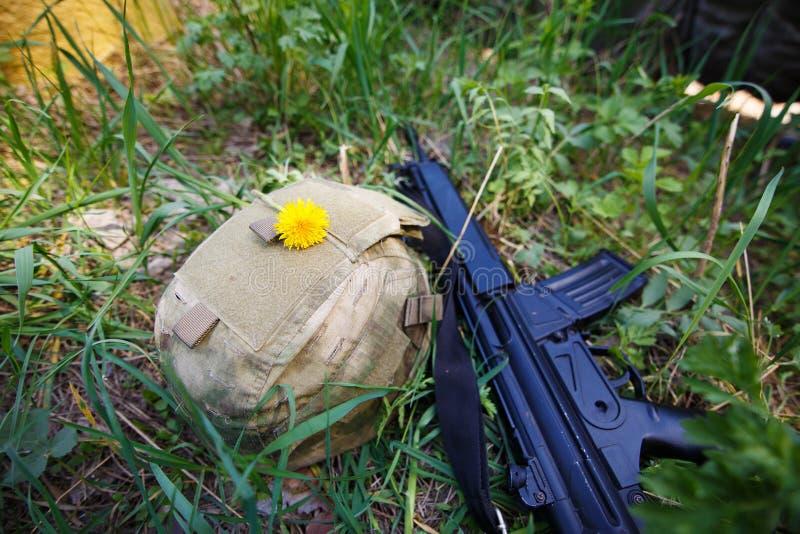Casque militaire, fusil et une fleur dans la fin d'herbe  images libres de droits