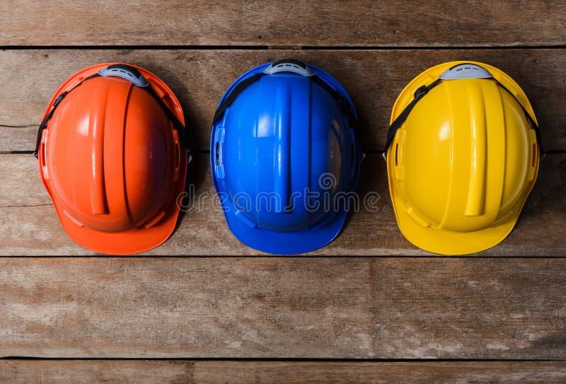 Casque protecteur de jaune, orange et bleu de sécurité photos stock