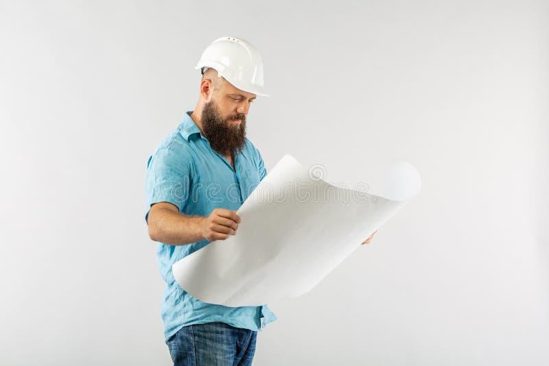 Casque réfléchissant de gilet d'homme de papier de petit pain l'architecte considère des dessins sur le fond de whute photos libres de droits