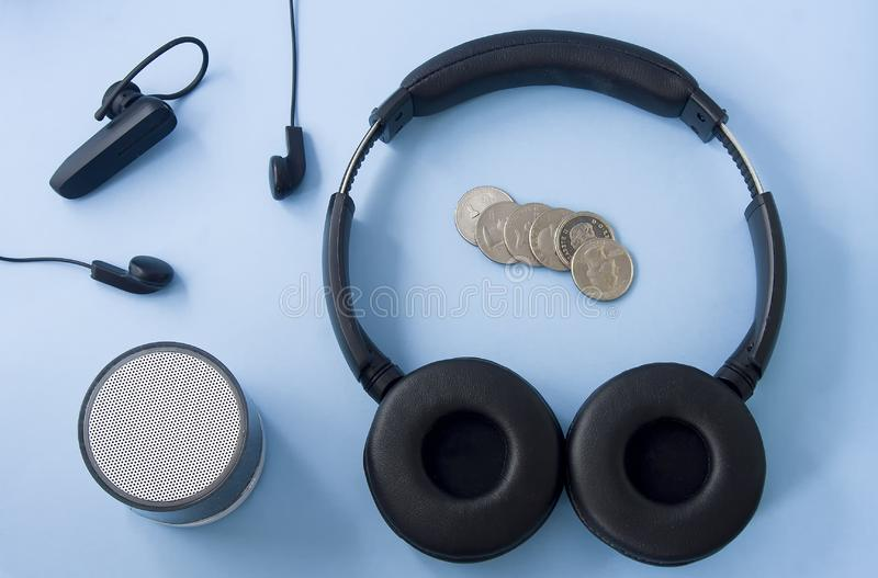 Casque sans fil, casque de câble, haut-parleur et pièces de monnaie photographie stock
