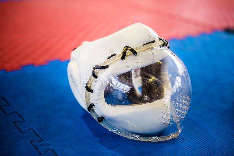 Casques de protection blancs avec le masque plactic clair pour des arts martiaux sur le plancher bleu rouge photographie stock libre de droits