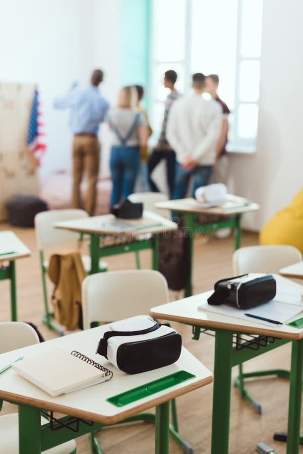Casques de réalité virtuelle sur les tables et le professeur avec des écoliers se tenant derrière photos libres de droits