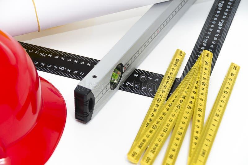 Casques et outils colorés pour les dessins de construction et le buildin images stock