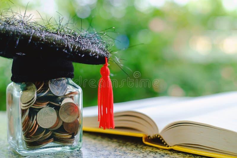 Casquillo académico cuadrado con el tarro de cristal de la moneda y del libro abierto o foto de archivo libre de regalías