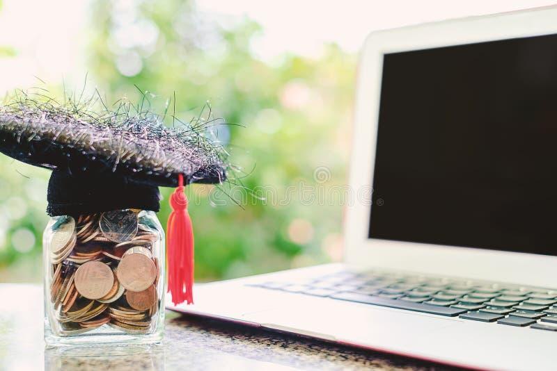 Casquillo académico cuadrado con el tarro de cristal de lapt de la moneda y del ordenador imagenes de archivo