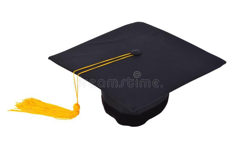 Casquillo de la graduación con la borla del oro aislada en el ingenio blanco del fondo fotos de archivo