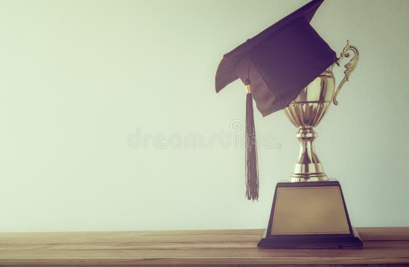 casquillo de la graduación con el trofeo de oro del campeón en la tabla de madera con el co foto de archivo
