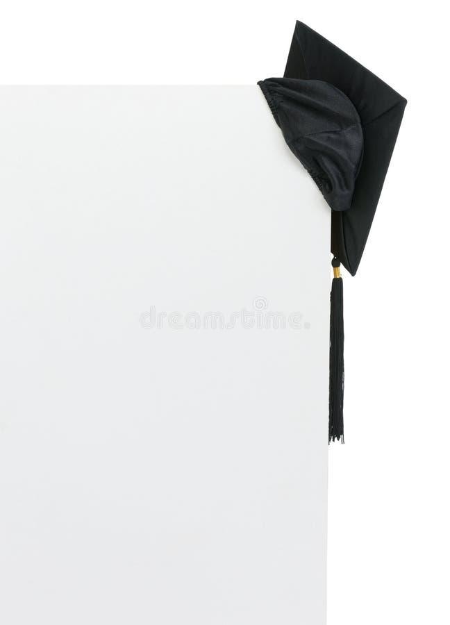 Casquillo de la graduación en la cartelera en blanco fotos de archivo libres de regalías