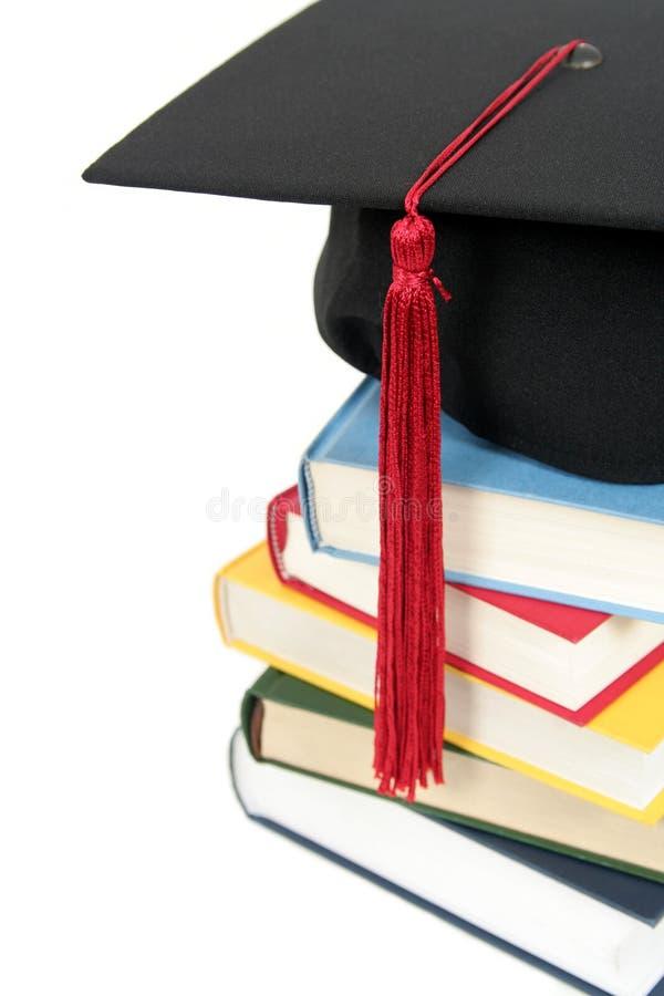 Casquillo de la graduación en la pila de libros imagen de archivo