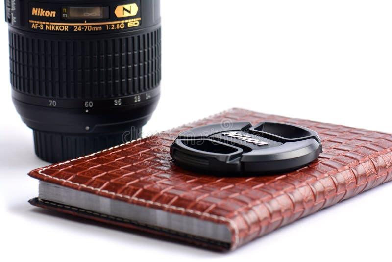 Casquillo de lente de Nikon en el cuaderno de cuero imagen de archivo libre de regalías