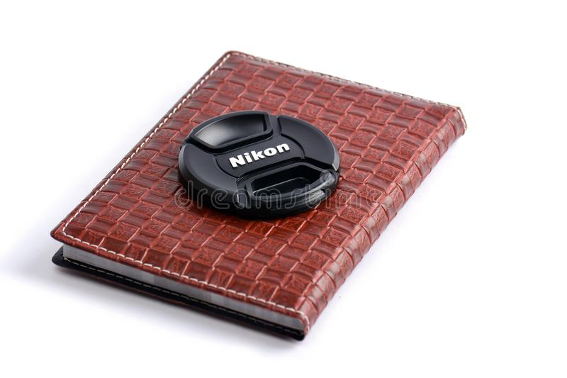 Casquillo de lente de Nikon en el cuaderno de cuero imágenes de archivo libres de regalías