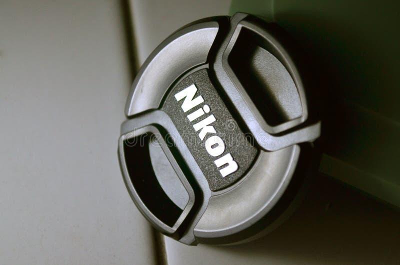 Casquillo de lente de Nikon en un piso en oscuro imagen de archivo