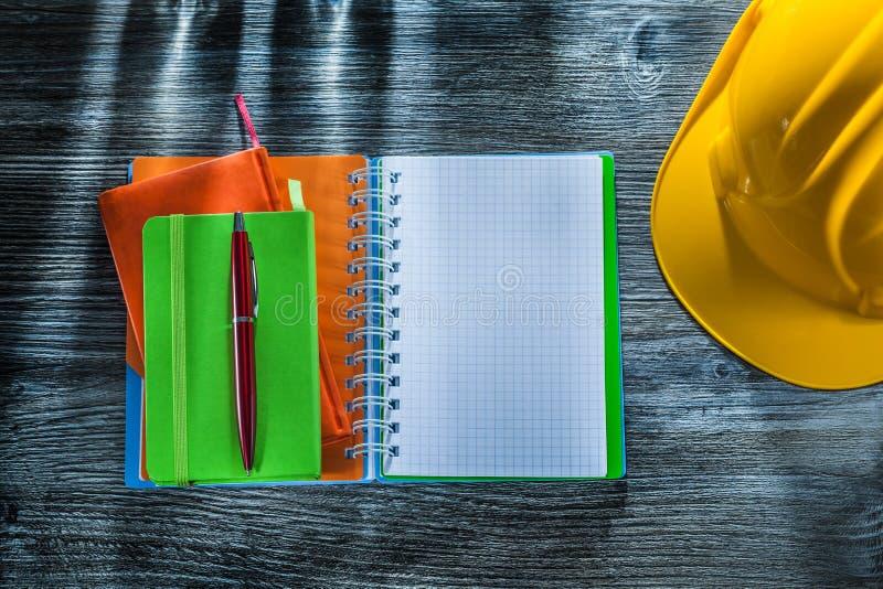 Casquillo de seguridad ajustado de la pluma de los cuadernos en el tablero de madera foto de archivo