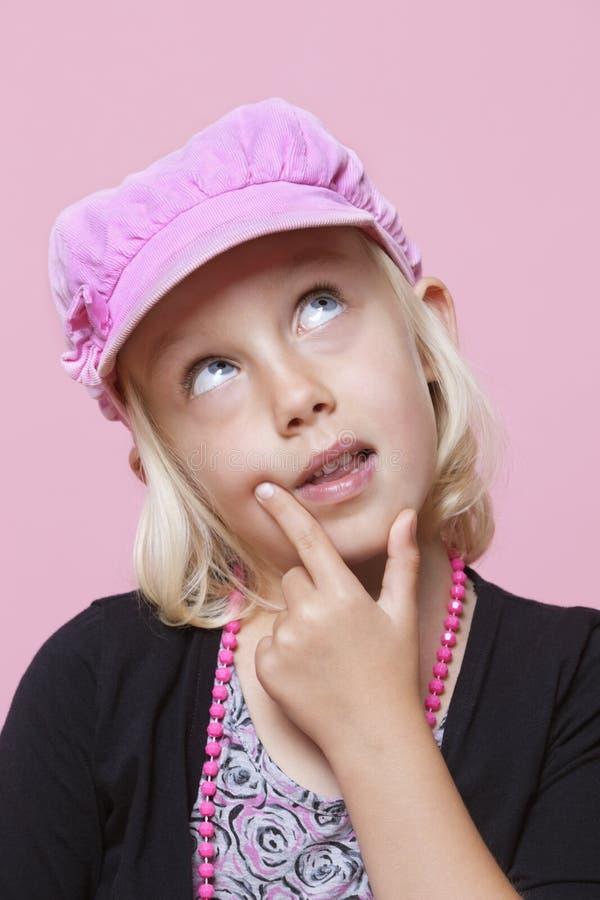Casquillo que lleva de la chica joven pensativa con el finger en la barbilla sobre fondo rosado fotografía de archivo libre de regalías