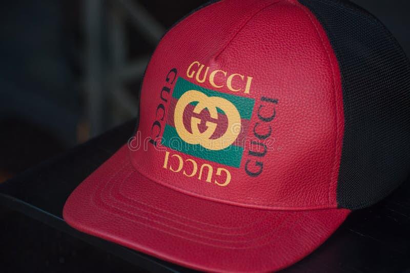 Casquillo rojo de Guci en la sala de exposición de la tienda de la moda imagen de archivo