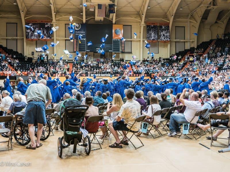 Casquillos azules del lanzamiento del curso de graduación de High School secundaria en el aire foto de archivo libre de regalías