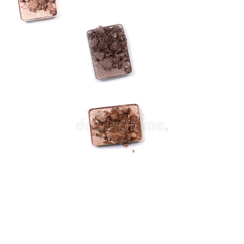Cassé composez et les produits cosmétiques Palette heurtée de fard à paupières dans des couleurs neutres d'isolement sur le  photos libres de droits