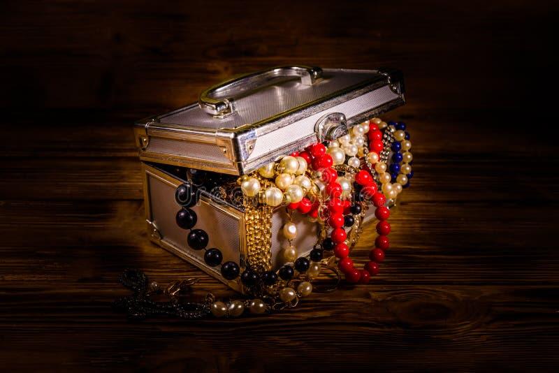 Cassa di alluminio in pieno di gioielli differenti sulla tavola di legno fotografia stock