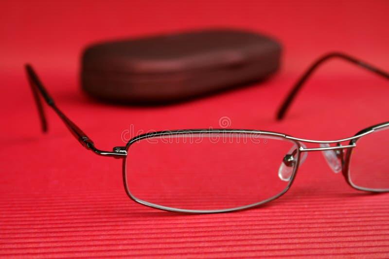 Cassa di vetro e degli occhiali su priorità bassa rossa fotografia stock