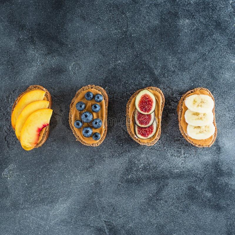 Casse-croûte avec du pain, le beurre d'arachide, les fruits frais et les baies Concept sain de nourriture Configuration plate, vu photographie stock