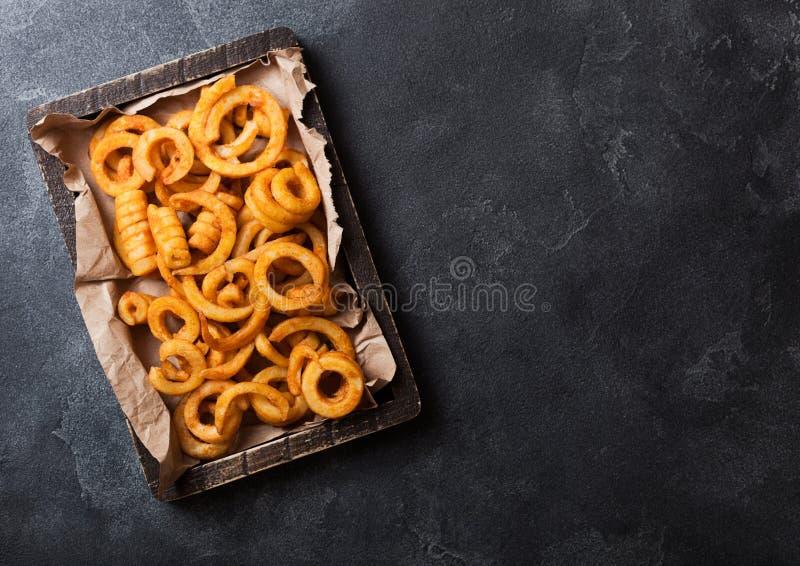 Casse-croûte bouclé d'aliments de préparation rapide de fritures dans la boîte en bois sur le fond en pierre de cuisine Nourritur photos stock
