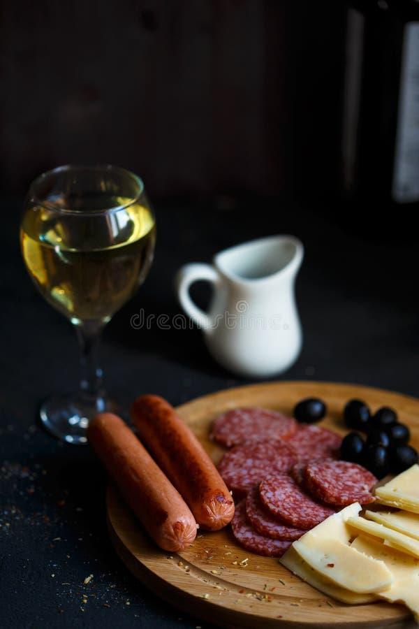 Casse-croûte de viande de table d'apéritif, saucisses frites, fromage, salami, olives et un verre de vin sur un menu de table et  photographie stock