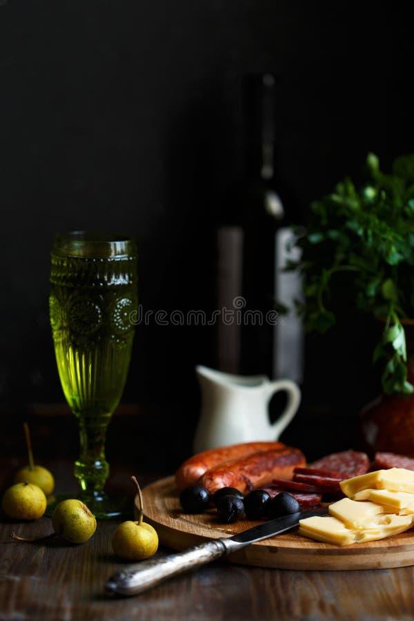 Casse-croûte de viande de table d'apéritif, saucisses frites, fromage, salami, olives et un verre de vin sur une table foncée photographie stock