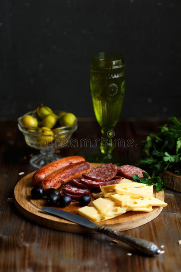 Casse-croûte de viande de table d'apéritif, saucisses frites, fromage, salami, olives et un verre de vin sur une table foncée Con photo stock