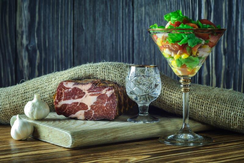 Casse-croûte modeste de viande avec de la salade végétale dans un verre de vin en verre à un tir de vodka sur un fond en bois gri photos libres de droits