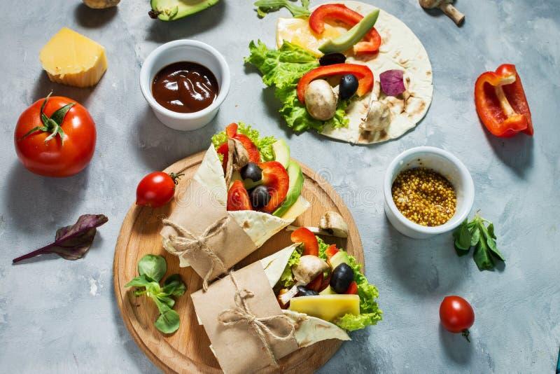 Casse-croûte sain de déjeuner de vegan Enveloppes de tortilla avec des champignons, des légumes frais et des ingrédients sur le f photographie stock