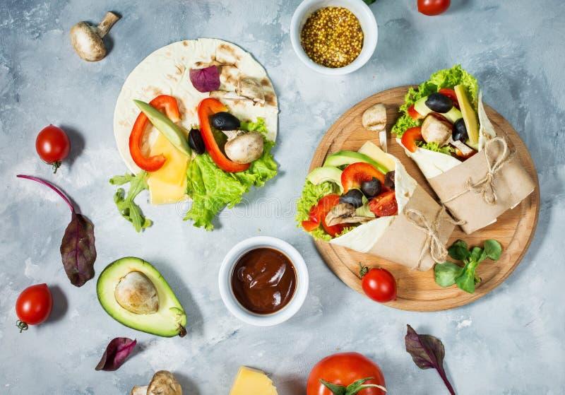 Casse-croûte sain de déjeuner de vegan Enveloppes de tortilla avec des champignons, des légumes frais et des ingrédients sur le f images stock