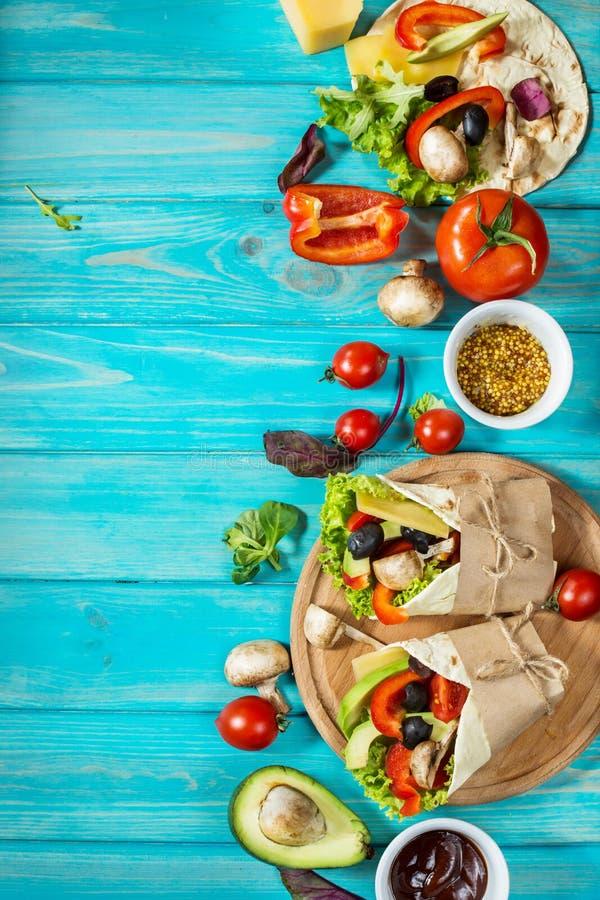 Casse-croûte sain de déjeuner de vegan Enveloppes de tortilla avec des champignons, des légumes frais et des ingrédients sur le f image libre de droits