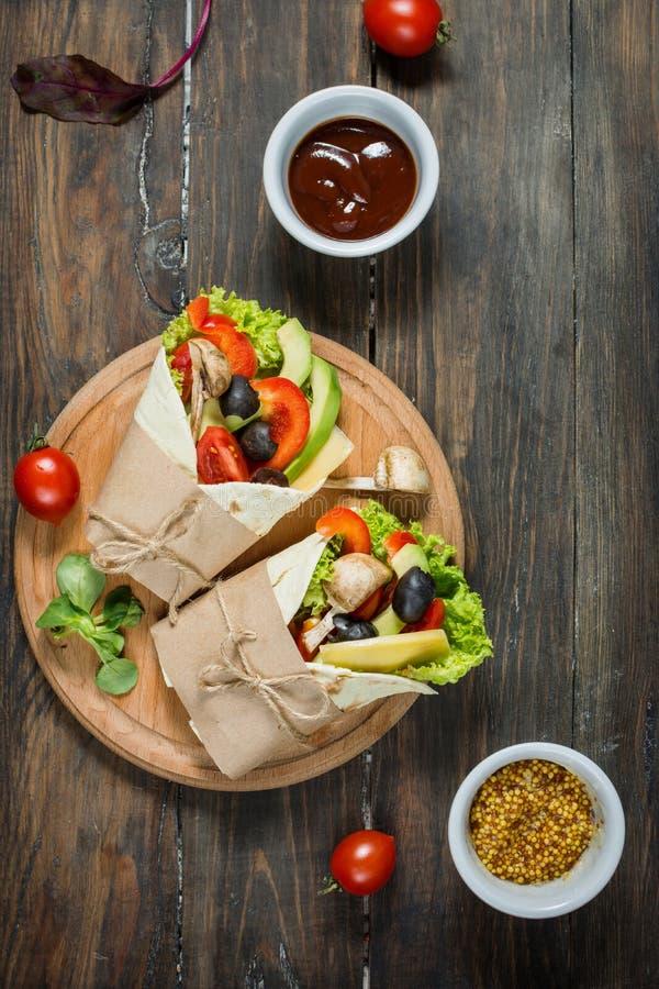 Casse-croûte sain de déjeuner de vegan Enveloppes de tortilla avec les champignons, légumes frais sur le fond en bois photos stock