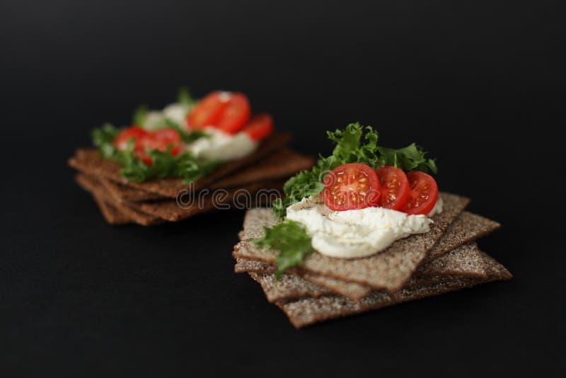 Casse-croûte sain du biscuit entier de pain croustillant de seigle avec les tomates-cerises, la salade et le fromage à pâte molle photo stock