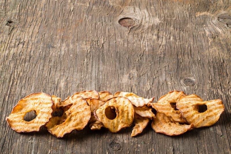 Casse-croûte sain La pomme sèche savoureuse sonne des puces sur le backgroun en bois image libre de droits