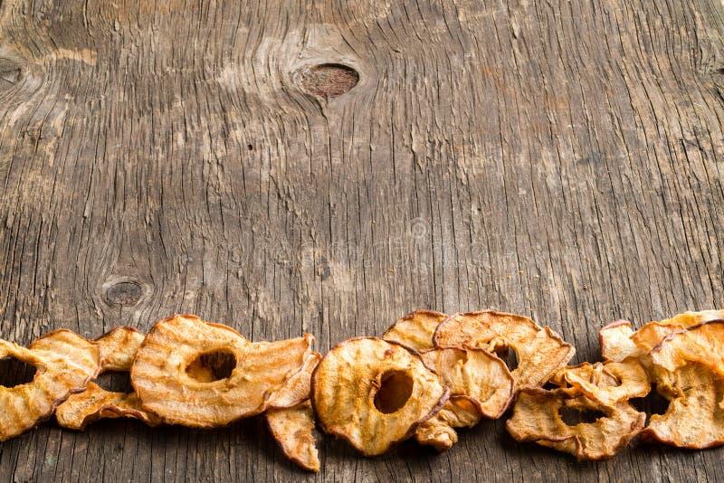 Casse-croûte sain La pomme sèche savoureuse sonne des puces sur le backgroun en bois photo stock